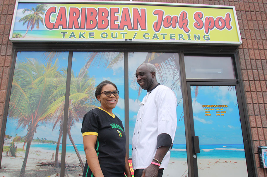 Lorna and Dennis Jarrett standing in front of their Jamaican restaurant signed Caribbean Jerk Spot
