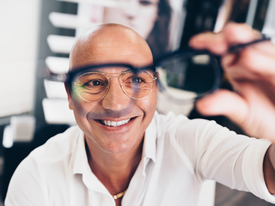 Bald man holding up a pair of glasses looking through one of the lenses