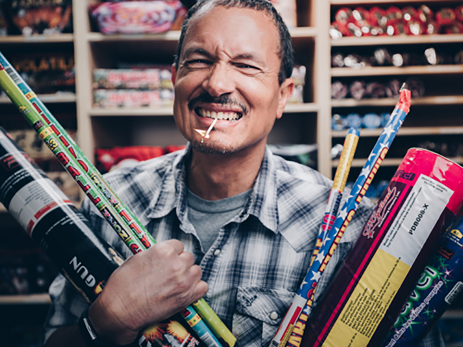 A man holding a bunch of fireworks in both arms with a lit match in his mouth