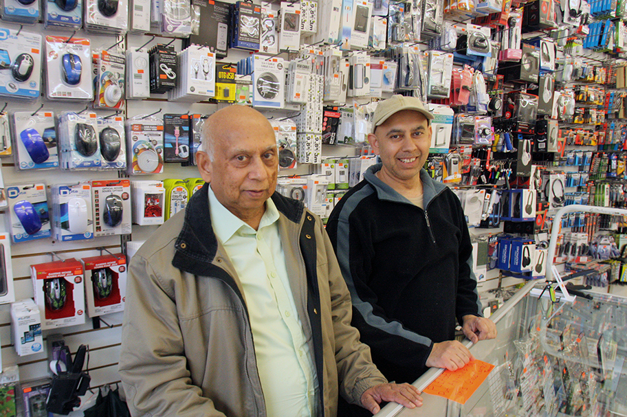 Photo of two men standing behind the counter at the dollar store they own. The wall if full of gadgets and items for sale.