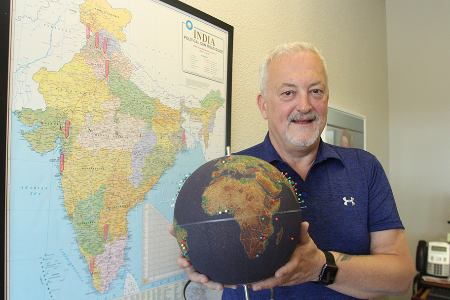 Photo of older man with grey hair holding a globe with colourful pins in it.