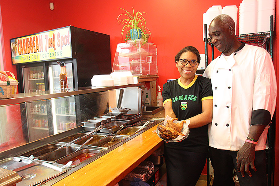 Photo of man and woman holding up a caribbean dish behind the counter in their colourful restaurant.